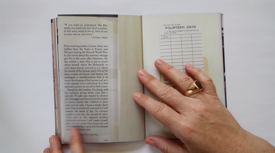 two hands holding open a small library book, left page has a blurb on it, right page has a due-date card. The right hand has a large gold ring on the right ring finger